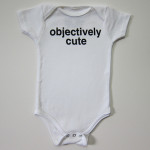 "A white onepiece for infants, with ""Objectively Cute"" in black block letters."