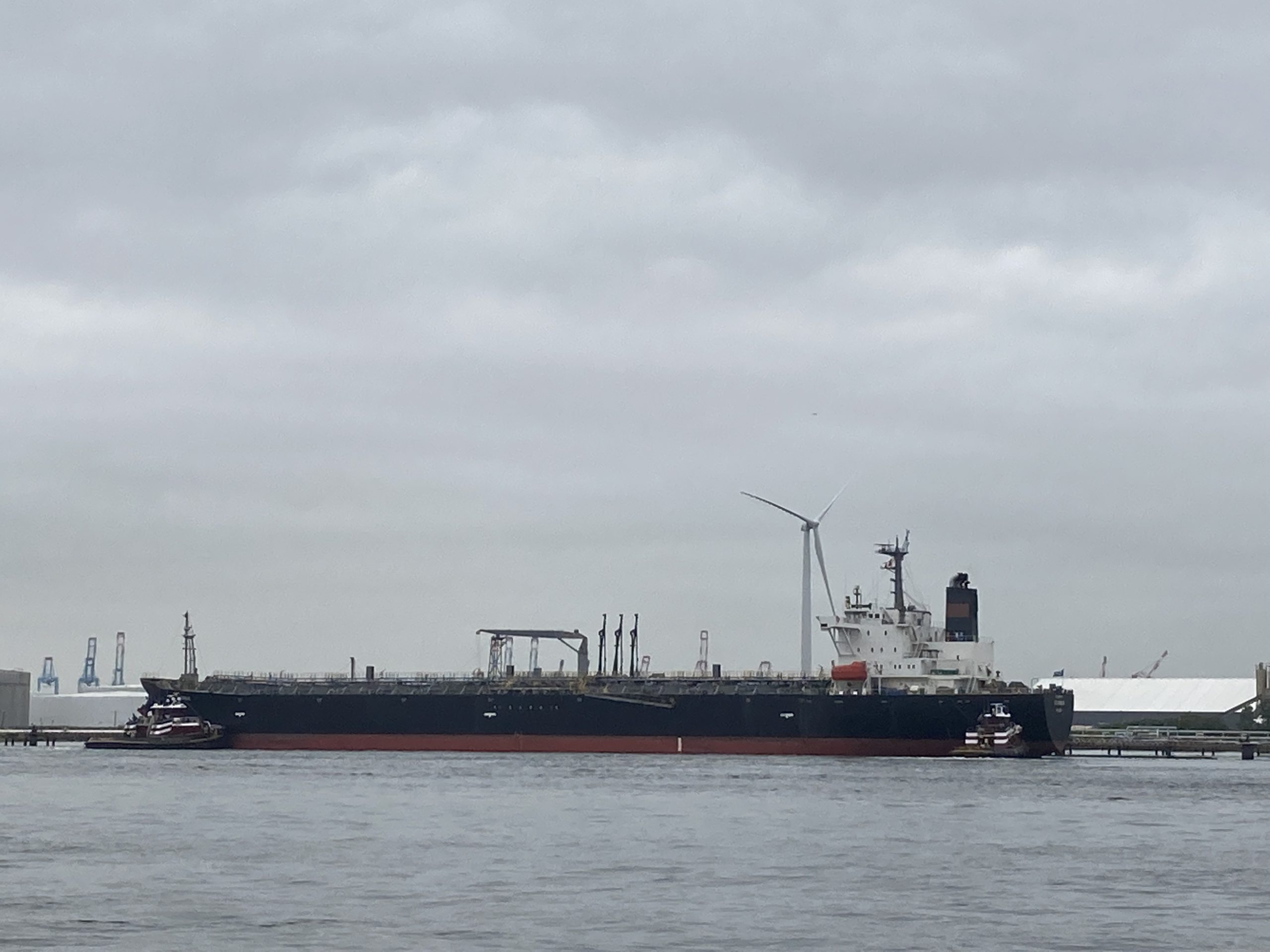 Black hulled freighter by a giant windmill on a windless, cloudy day.